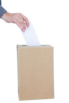 ビジネスマン、投票箱に投票用紙を置く