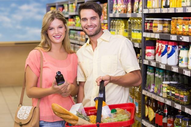 買い物カゴを使用して食品を購入する笑顔の明るいカップルの肖像