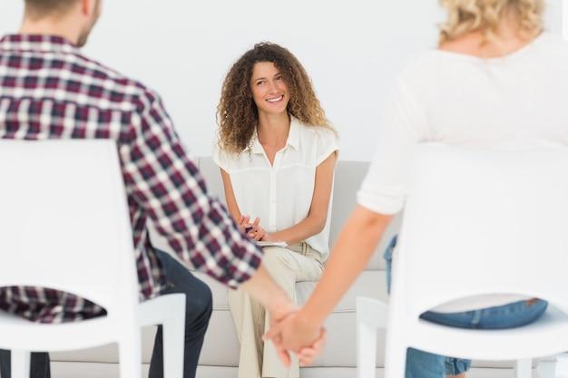 手を握って和解したカップルに笑っているハッピーセラピスト