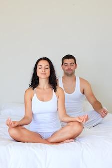 ベッドで瞑想するカップル