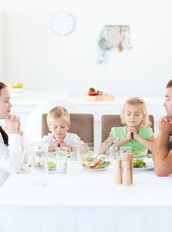 Родители и их дети молятся во время обеда