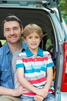 Счастливый отец и сын, сидящий в багажнике автомобиля
