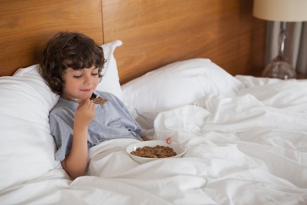 ベッドで朝食を食べる若い少年