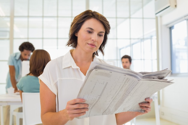 会議の同僚と新聞を読んでいるビジネスマン