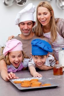 子供と両親がベーキング後にクッキーを食べる