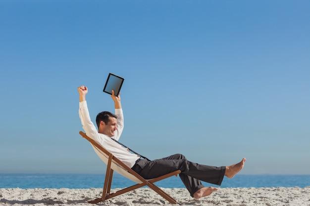 勝利の若い実業家が彼のデッキの椅子に座って彼のタブレットを保持