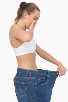 あまりにも大きいジーンズを着て驚いたスリムな若い女性
