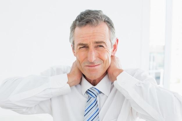 首の痛みに苦しんでいる成熟した男の肖像