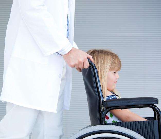医者がサポートしている車椅子に座っている笑っている少女