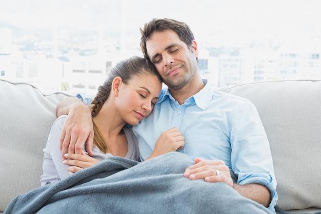 毛布の下でソファでリラックスしている明るいカップル