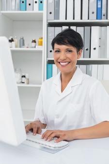 Уверенный улыбается женщина-врач, используя компьютер