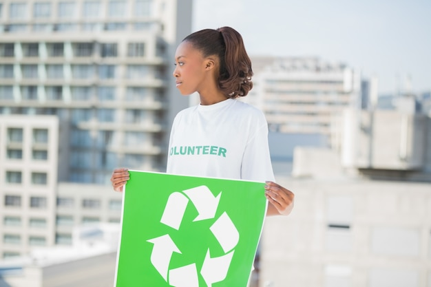 かわいいボランティアの女性がリサイクルのサインを探して