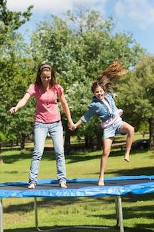 Счастливая девушка и мать прыгают высоко на батуте в парке