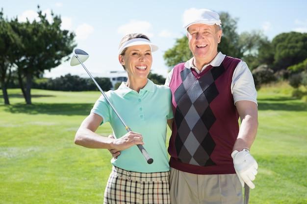 カメラで笑っているゴルフカップル
