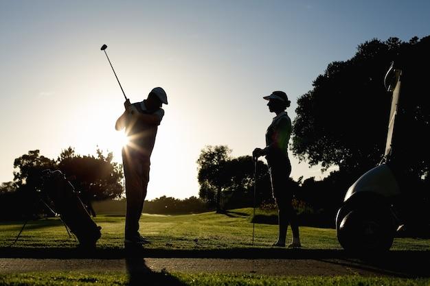 ゴルフのカップルが一日オフにティーオフ