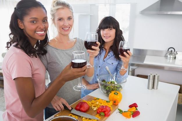 一緒に食事を準備し、赤ワインを飲む陽気な友人