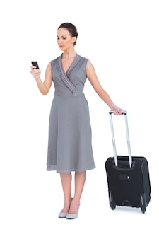 彼女のスーツケースの文字メッセージで真面目な豪華な女性