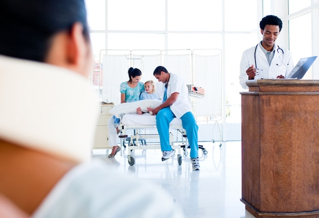 車椅子、仕事中の医療チームに座って負傷した女性
