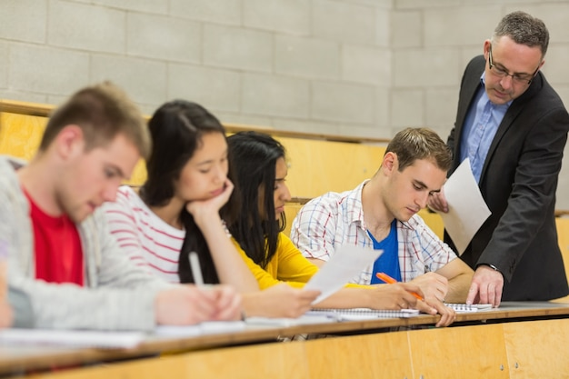 Учитель со студентами, записывающими заметки в лекционный зал