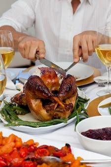 Крупный план человек, сокращая индейку на рождественский ужин