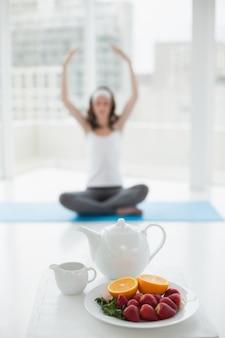 Размытые женщины в медитации осанка со здоровой пищи на переднем плане