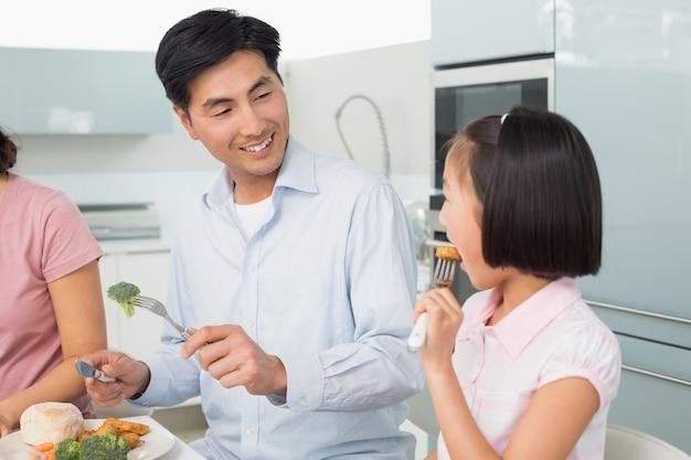 小さな女の子がキッチンのフォークで食べ物を食べるのを見る父