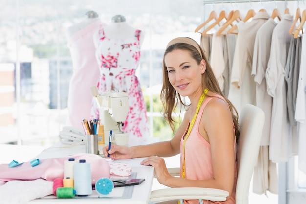 彼女のデザインに取り組んでいる女性ファッションデザイナーの肖像