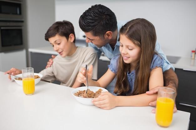父親と朝食を楽しむ幸せな若い子供たち