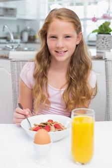 キッチンで朝食を取る若い女の子
