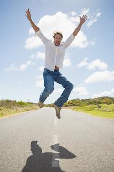 Красивый случайный человек прыгает на дороге, улыбаясь на камеру