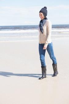 ビーチで歩いているジーンズのかなりのブロンド