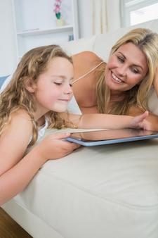 Дочка и мать, использующие планшет