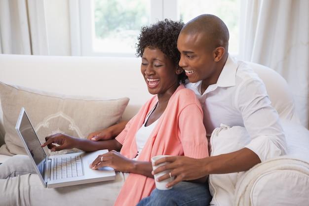 コーヒーを持つラップトップを使ってソファーで一緒にリラックスしている幸せなカップル