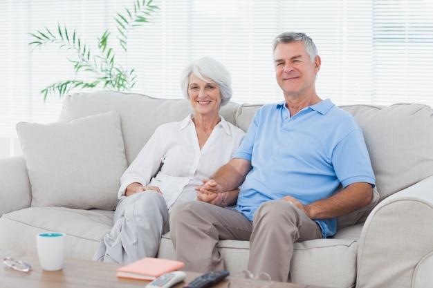 Пожилая пара, сидя на диване