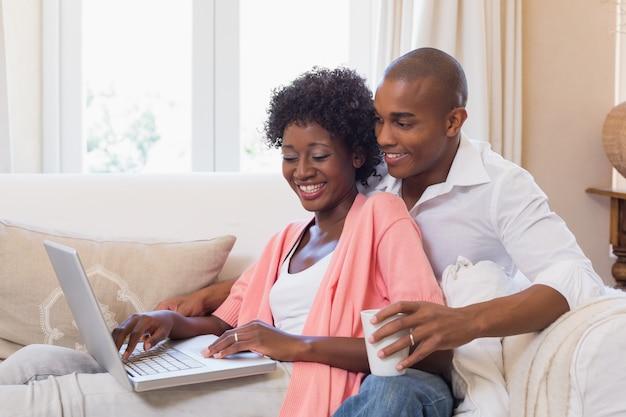 かわいいカップルは、ノートパソコンとコーヒーのソファでリラックス