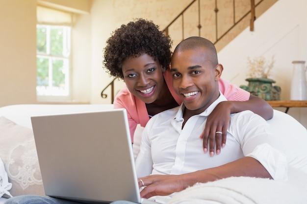 かわいいカップルは、ノートパソコンでソファーでリラックス
