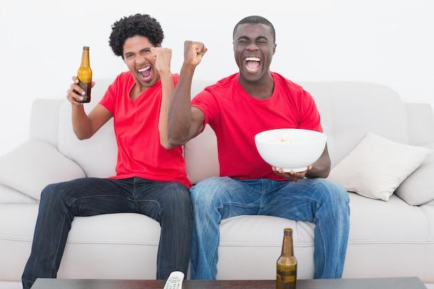 ビールとポップコーンでソファに座っている赤いサッカーファン