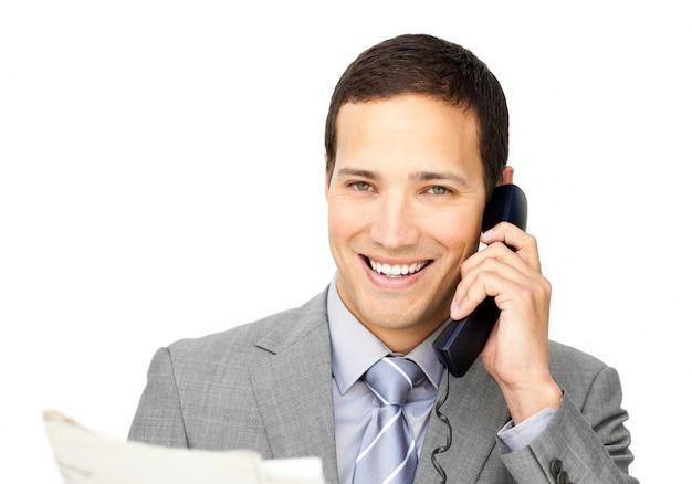 新聞を持って電話で魅力的なビジネスマン