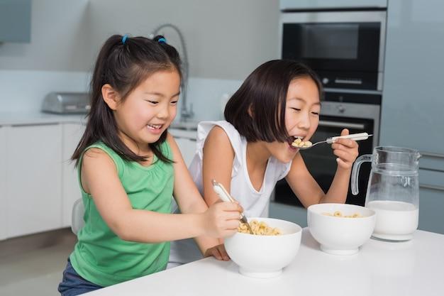 二人の笑顔の若い女の子が穀物を食べる