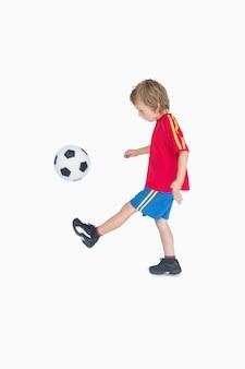 Боковой вид мальчика, пинающего футбол