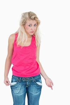 彼女の空のポケットを見せている悲しい若い女性