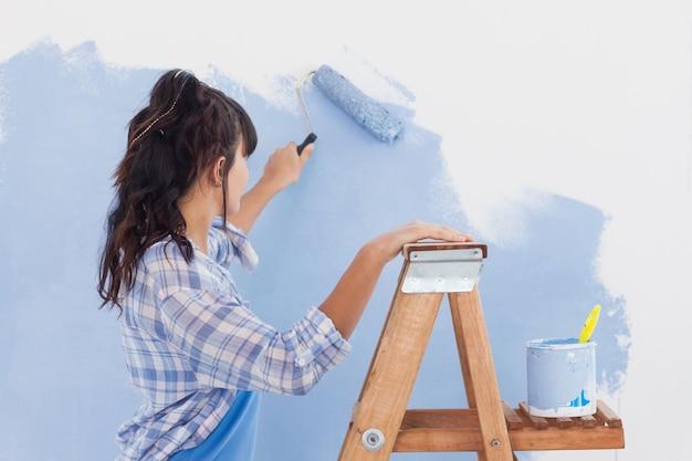 ペイント・ローラーを使って壁をペイントする女性