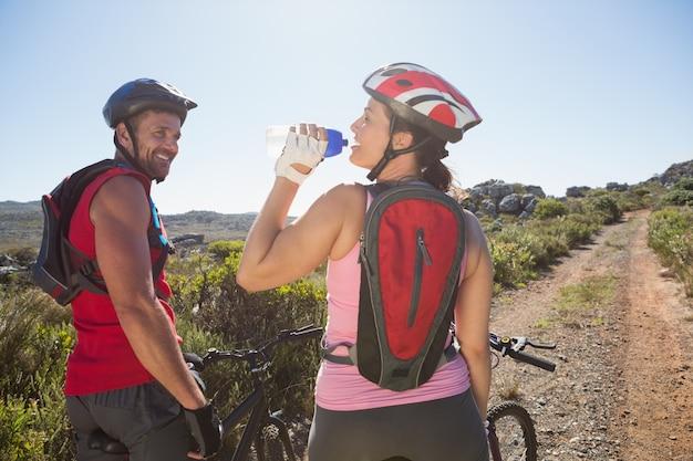 田舎の自転車に乗っているアクティブなカップル