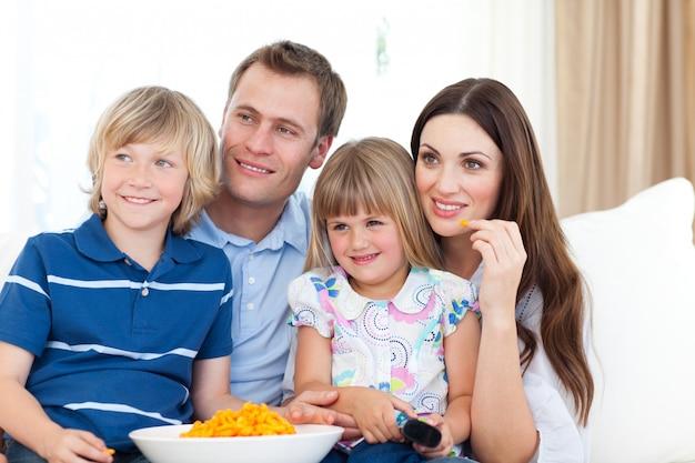 Семья смотрит телевизор и ест чипсы