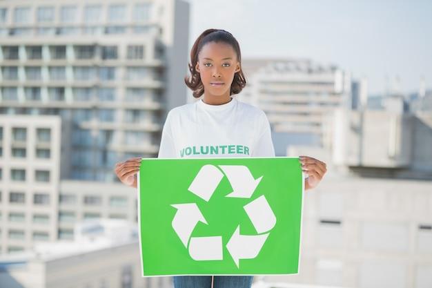 深刻なボランティアの女性がリサイクルのサインを持っている