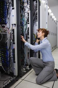 深刻な技術者は、サーバーを分析しながら電話で話す