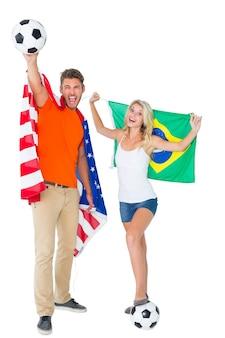 アメリカとブラジルの旗を掲げている興奮したサッカーファンのカップル