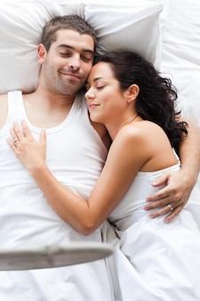 少年とベッドに横たわっている若い女性