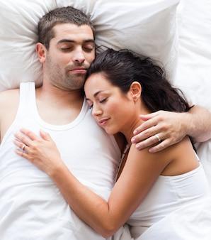 ベッドに横たわっている愛するカップル