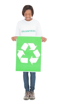 リサイクルサインを持っている幸せなボランティアの女性